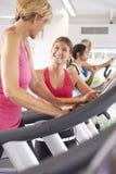 Mujer en la máquina corriente en el gimnasio alentador por el instructor personal imagen de archivo