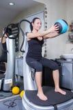 Mujer en la máquina del amaestrador en gimnasia del deporte Fotos de archivo