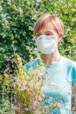 Mujer en la máscara de la protección que sostiene el ramo de wildflowers y de tryi imagen de archivo