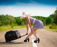 Mujer en la maleta del camino, vestido rayado azul, sombrero blanco, hei lleno Fotos de archivo