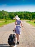 Mujer en la maleta del camino, vestido rayado azul, sombrero blanco, heig completo Fotografía de archivo libre de regalías