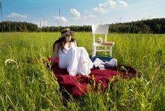 Mujer en la manta roja de la comida campestre Foto de archivo