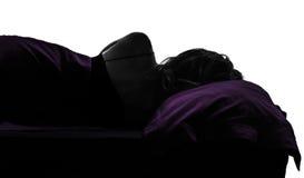 Mujer en la mentira el dormir de la cama en silueta lateral Imagen de archivo