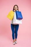 Mujer en la mirada básica que celebra bolsos después de hacer compras en la alameda Fotografía de archivo libre de regalías