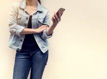 Mujer en la moda de los vaqueros que sostiene el teléfono móvil Fotografía de archivo