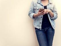Mujer en la moda de los vaqueros usando el teléfono móvil Fotos de archivo libres de regalías