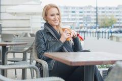 Mujer en la moda negra que come café en el café Foto de archivo libre de regalías