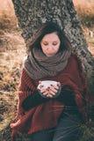 Mujer en la naturaleza que sostiene la taza Foto de archivo libre de regalías