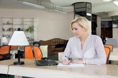 Mujer en la oficina con un ordenador portátil Fotos de archivo libres de regalías