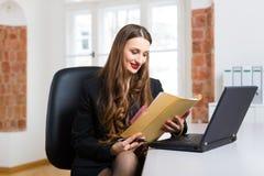 Mujer en la oficina que se sienta en el ordenador Imagen de archivo