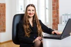 Mujer en la oficina que se sienta en el ordenador Fotos de archivo