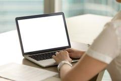 Mujer en la oficina que trabaja en el ordenador portátil con la pantalla en blanco de la maqueta imagen de archivo