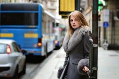 Mujer en la parada de autobús fotos de archivo