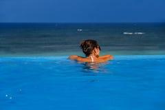 Mujer en la piscina del infinito Imagen de archivo