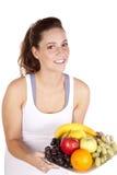 Mujer en la placa blanca de la fruta de la explotación agrícola de la tapa del tanque Imágenes de archivo libres de regalías