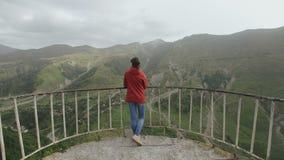 Mujer en la plataforma de observación la vista del valle de la montaña con una garganta, picos de montaña, acantilados metrajes