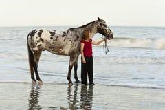 Mujer en la playa con appaloosa Foto de archivo libre de regalías