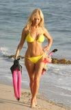 Mujer en la playa con el engranaje de equipo de submarinismo Fotos de archivo libres de regalías