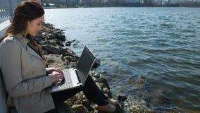 Mujer en la playa con el ordenador portátil almacen de video