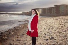 Mujer en la playa con una capa roja imagen de archivo
