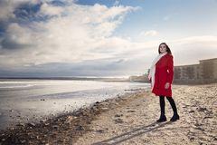 Mujer en la playa con una capa roja foto de archivo