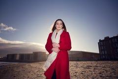 Mujer en la playa con una capa roja imagenes de archivo