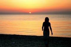 Mujer en la playa en la puesta del sol Fotos de archivo