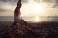 Mujer en la playa en la puesta del sol imágenes de archivo libres de regalías