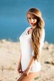 Mujer en la playa en un vestido blanco corto Foto de archivo