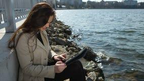 Mujer en la playa, leyendo la tableta y metrajes