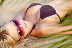 Mujer en la playa, poniendo bajo el sol Imagenes de archivo