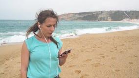 Mujer en la playa que escucha la música en los auriculares del teléfono elegante Nazare, Portugal metrajes