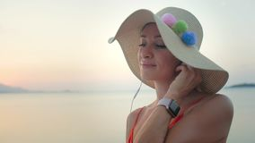 Mujer en la playa que escucha la música en los auriculares del smartphone almacen de metraje de vídeo