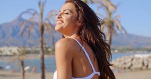 Mujer en la playa que lanza el pelo detrás con los ojos cerrados almacen de metraje de vídeo