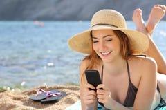 Mujer en la playa que manda un SMS a un teléfono elegante en verano Foto de archivo