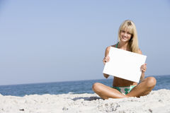 Mujer en la playa que sostiene la tarjeta en blanco Imagen de archivo libre de regalías