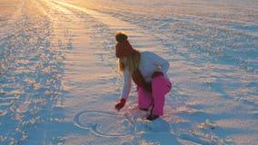 Mujer en la puesta del sol en un día de invierno en la pintura de la nieve con el corazón 4k de la mano almacen de video