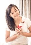 Mujer en la ropa blanca que sostiene el juguete de Papá Noel disponible imagen de archivo libre de regalías