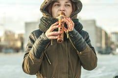Mujer en la ropa caliente que toca una flauta del instrumento musical al aire libre en una tarde soleada afuera imagenes de archivo