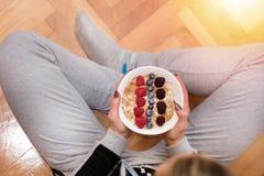 Mujer en la ropa casera que come las gachas de avena de la avena en el cuenco adornado con las zarzamoras, las frambuesas y los a imagen de archivo