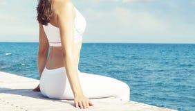 Mujer en la ropa de deportes blanca que hace yoga en un embarcadero de madera Mar y Fotografía de archivo