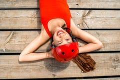 Mujer en la ropa de deportes que descansa sobre los tableros de madera Imagenes de archivo