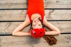 Mujer en la ropa de deportes que descansa sobre los tableros de madera Fotos de archivo libres de regalías