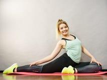 Mujer en la ropa de deportes que estira las piernas Imagen de archivo libre de regalías