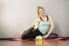 Mujer en la ropa de deportes que estira las piernas Foto de archivo libre de regalías