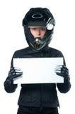 Mujer en la ropa de la motocicleta que lleva a cabo a una tarjeta blanca Imagen de archivo libre de regalías