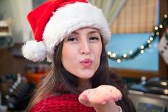 Mujer en la ropa de la Navidad que sopla un beso Fotos de archivo libres de regalías