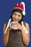 Mujer en la ropa del invierno que sostiene una taza Foto de archivo libre de regalías