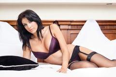 Mujer en la ropa interior atractiva que presenta en cama Imágenes de archivo libres de regalías