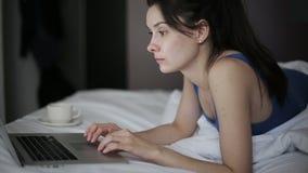 Mujer en la ropa interior que practica surf Internet con su ordenador portátil en una habitación tiro del steadicam almacen de metraje de vídeo